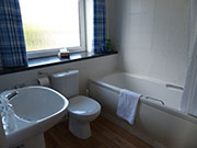 Ensuite bathroom with bath and mains pressure shower.